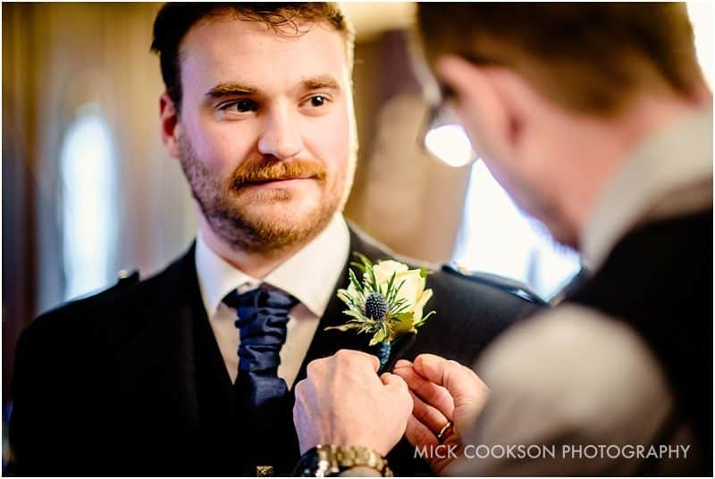 groomsman putting on button hole