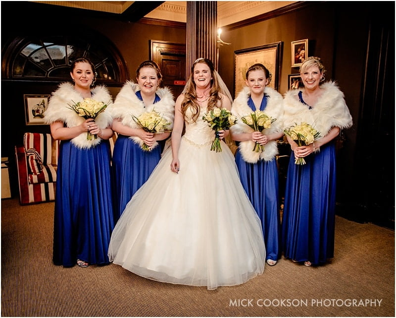bride and bridesmaids laughing inside eaves hall