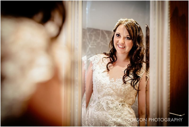 lancashire bride looking at herself in the mirror