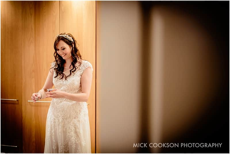 smiling bride putting perfume on