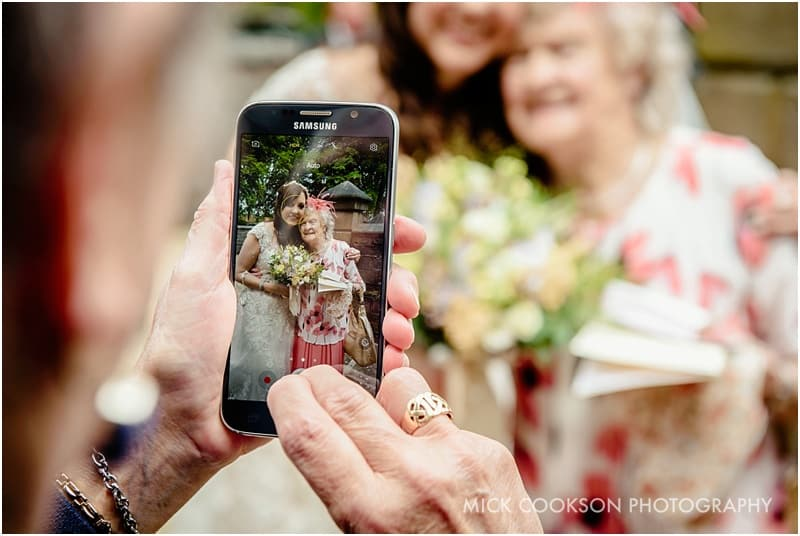 photo of bride and grandma on a mobile phone