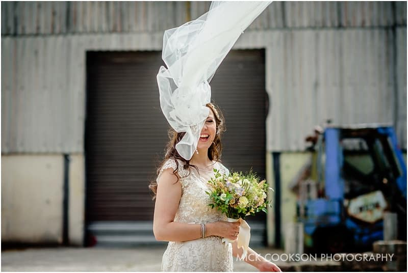 laughing bride as wind blows her veil