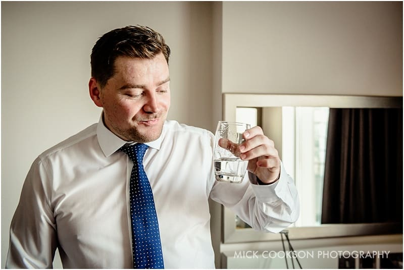 groom tasting gin on his wedding day