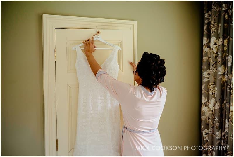 bride hanging her wedding dress up