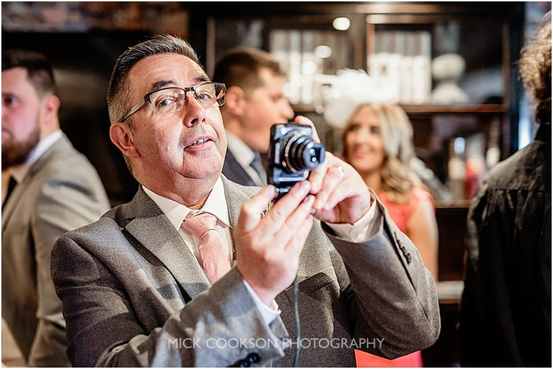 father of the groom taking a photo