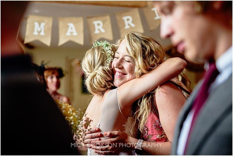 bride hugs a wedding guest at charnock farm