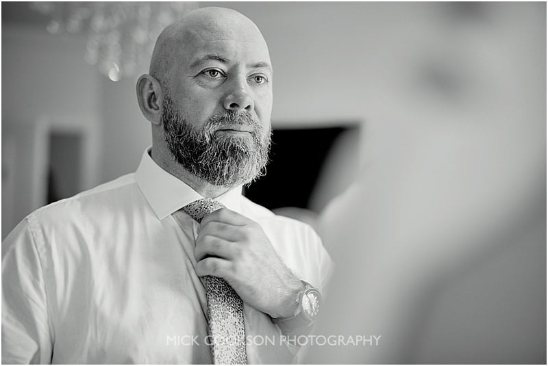 groom adjusting his tie at colshaw hall