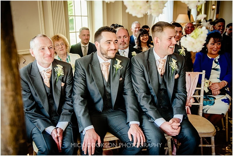 groomsmen smiling during the wedding ceremony