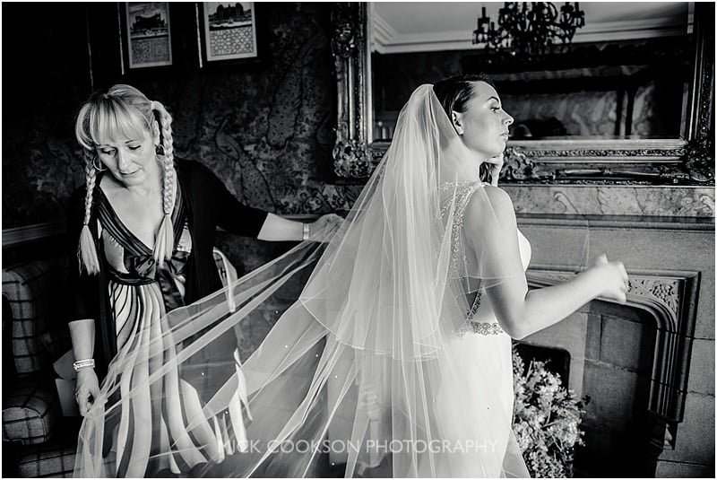 putting the wedding dress on at a mitton hall wedding