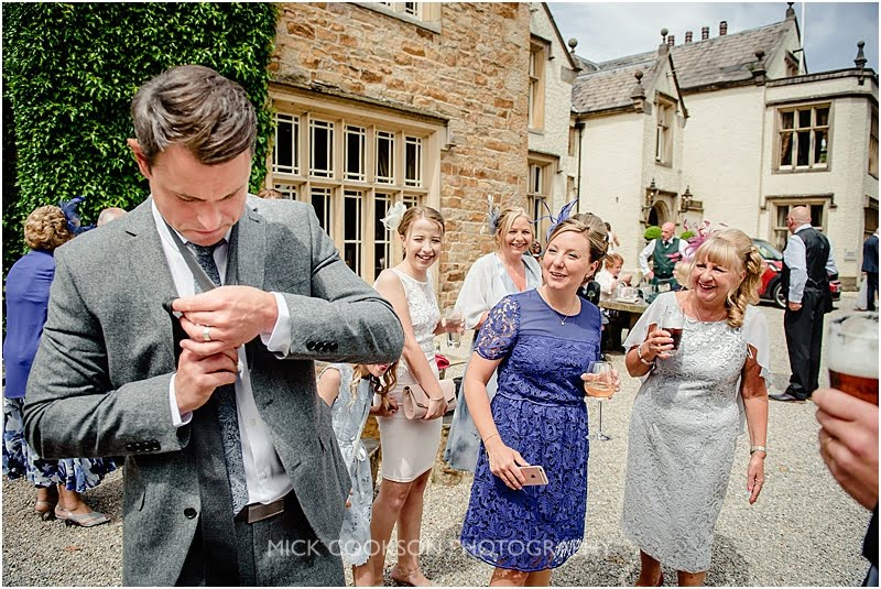 wedding guests struggling to tie his own tie