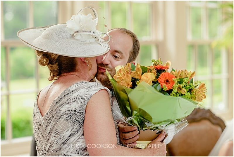 groom kisses mum at a mitton hall wedding