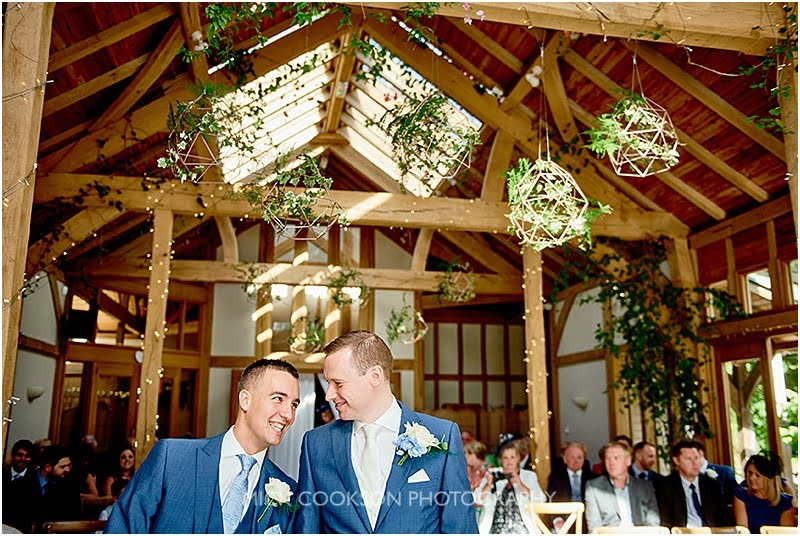 groom and best man share a joke at an oak tree of peover wedding
