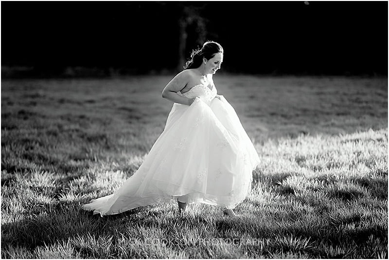 bride running through a field at the oak tree of peover