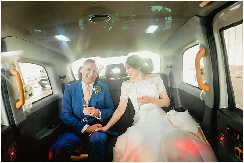 bride and groom in i do taxi at their manchester wedding taken by manchester wedding photographer mick cookson