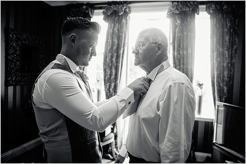 groom fastening his father's tie at an eves hall wedding