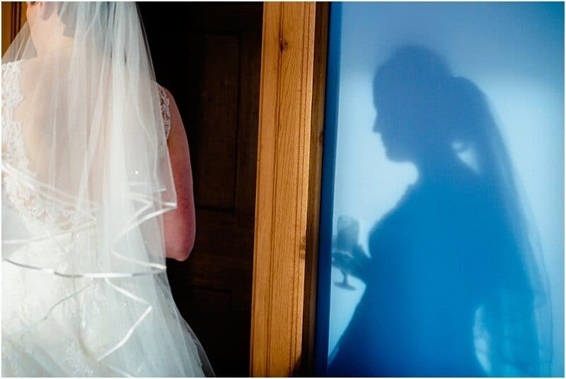 bride shadow on a blue wall at haigh hall taken by manchester wedding photographer mick cookson