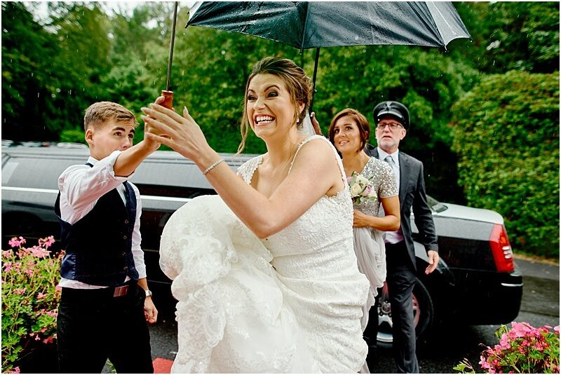 excited bride arrives in the rain for her bartle hall wedding taken by manchester wedding photographer mick cookson