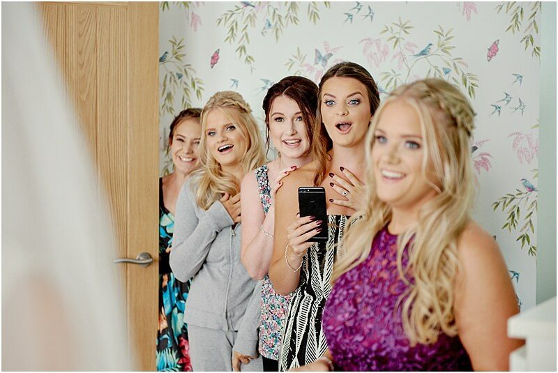 excited bridesmaids see the bride for the first time taken by manchester wedding photographer mick cookson