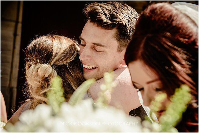 groom hugs a bridesmaid