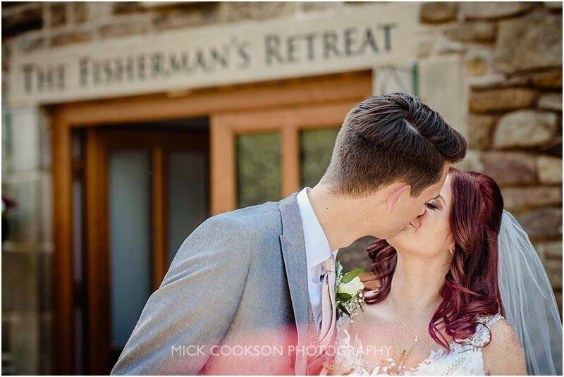 bride and groom kiss outside the fishermans retreat